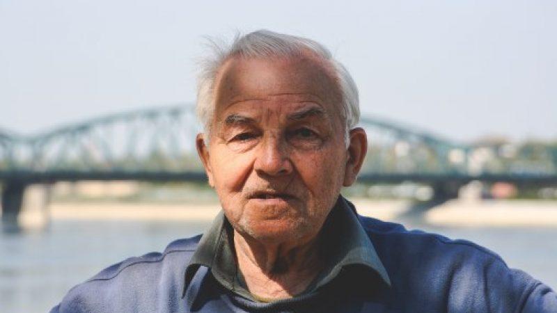 Older man standing in front of a bridge
